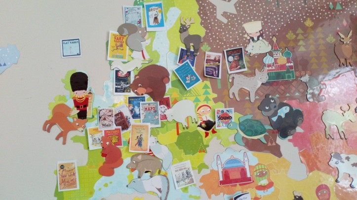 Picture of a world map with images of book covers stuck on it showing the origin of the books